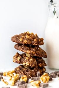Four double chocolate chip cookies stacked with walnuts and a glass of milk with a straw in it
