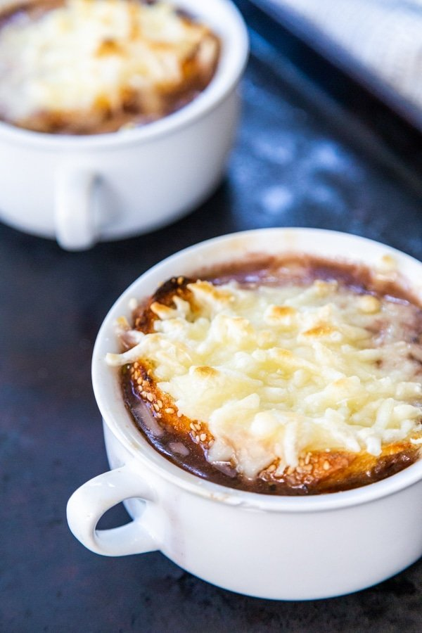 Two white bowls of French onion soup with melted cheese on top.