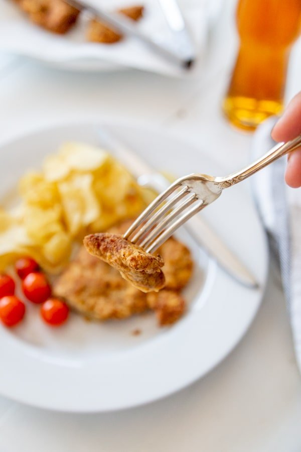 A hand cutting a piece of fried chicken with a fork.