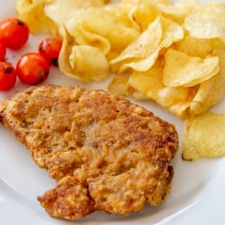A piece of fried chicken, chips, and tomatoes on a white plate.