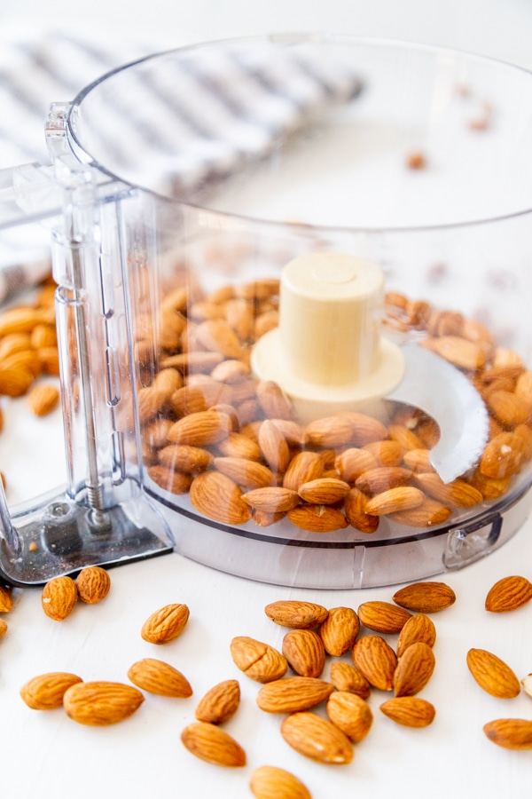 Almonds in a food processor with almonds spread on a white board.