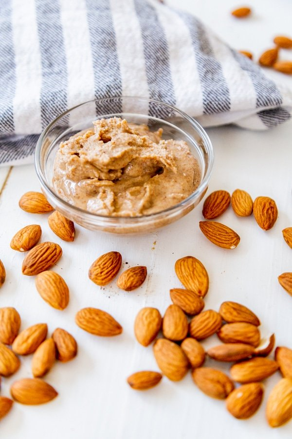 A glass dish filled with almond butter and almonds and a striped towel on a white wood table.