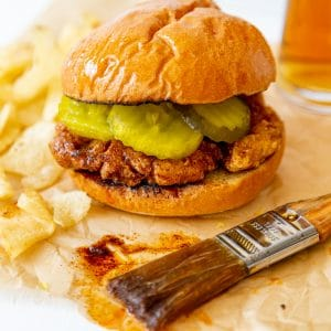 A spicy fried chicken sandwich on parchment paper with a pastry brush dripping spicy sauce next to it.