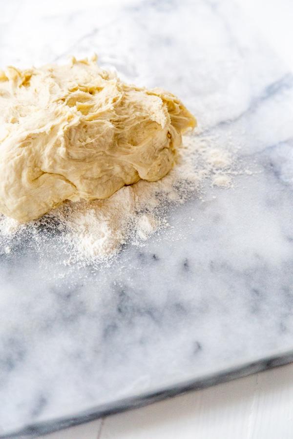 A marble slab with flour and pizza dough.