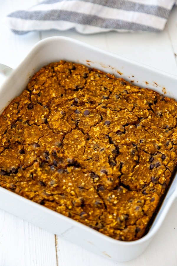 Pumpkin chocolate chip blondies in a square white baking dish.