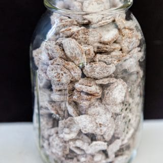 A clear mason jar filled with puppy chow snacks.