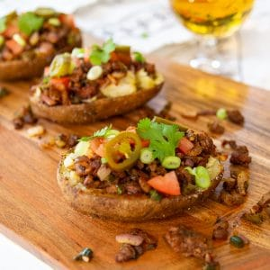 Three loaded stuffed potatoes on a wood board with a glass of beer.