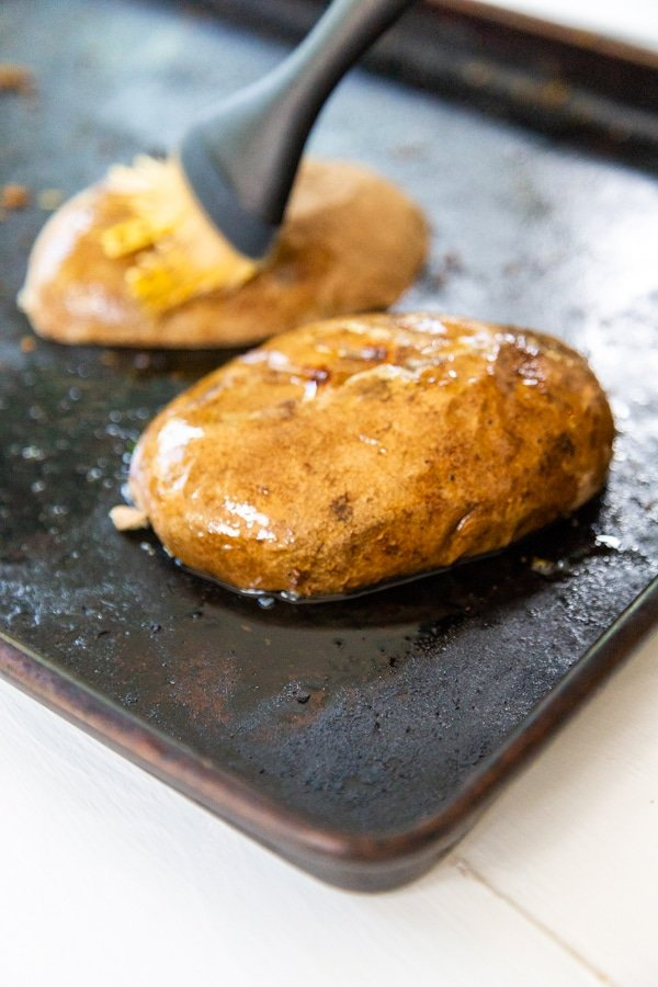 Baked potatoes being brushed with oil.