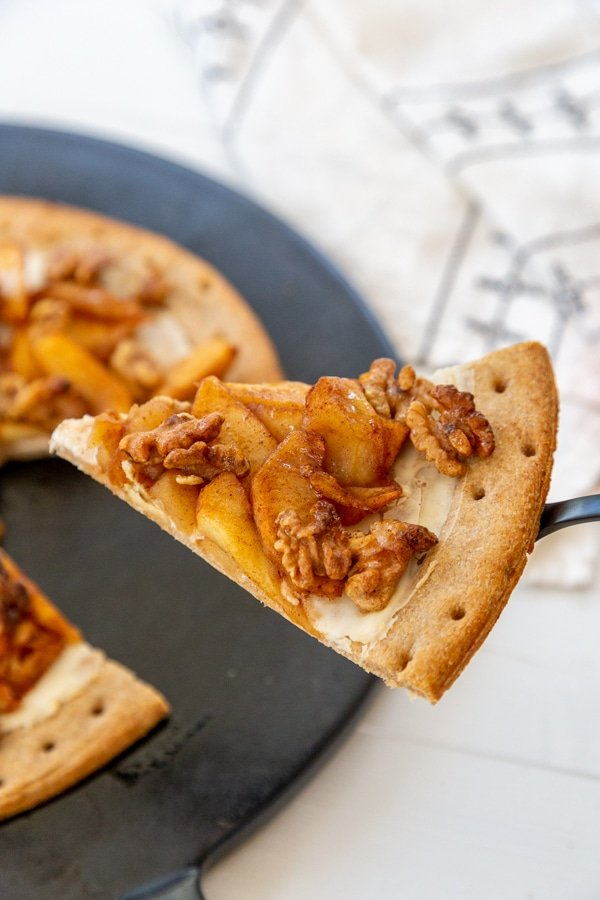 A slice of apple pizza on a serving utensil being lifted from the pizza stone.