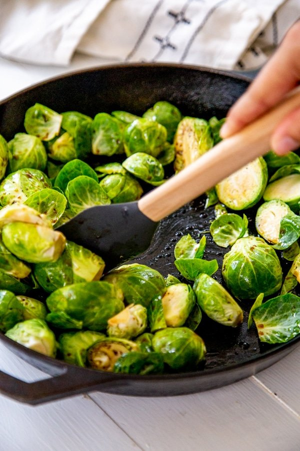 A hand stirring oil and Brussels sprouts in a skillet.