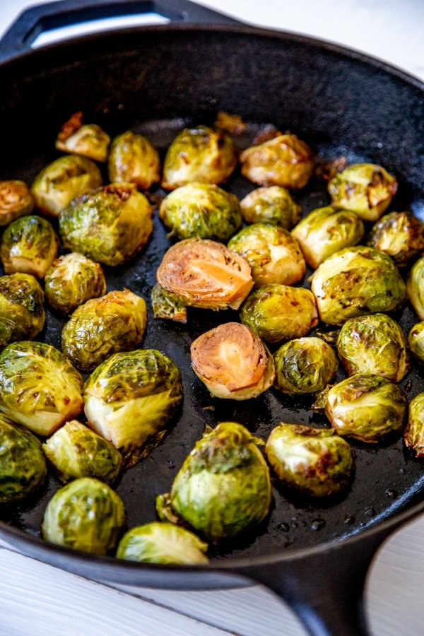 Roasted Brussels sprouts in a black iron skillet.