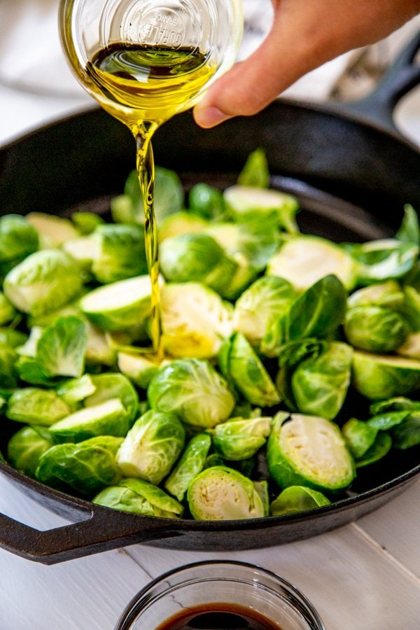 A hand drizzling olive oil over a skillet of Brussels sprouts.