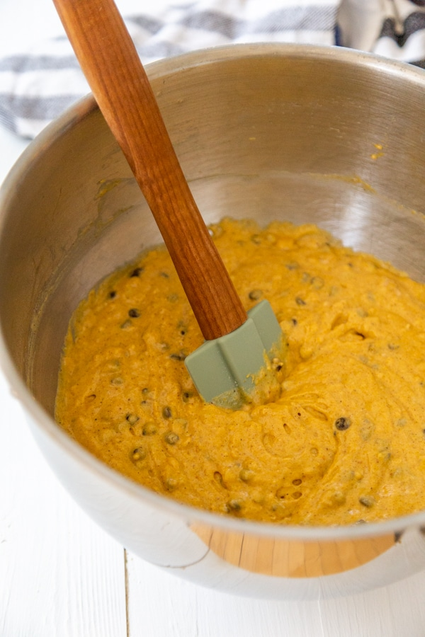 A silver mixing bowl with a spatula stirring chocolate chips into pumpkin bread batter.