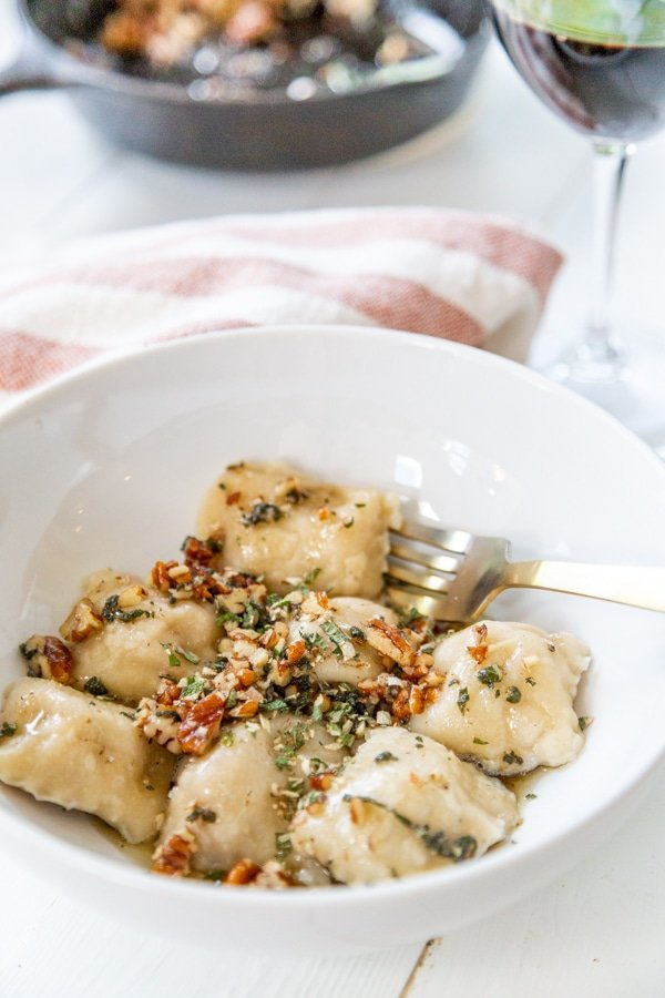 A white bowl of ravioli with brown butter and pecans on top.