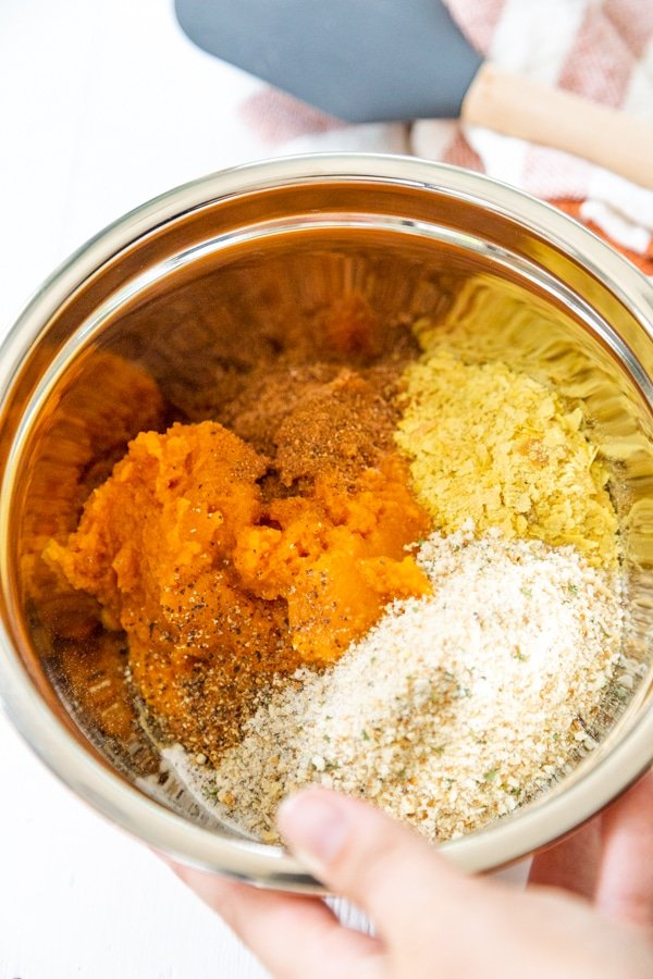 A hand holding a bowl of pumpkin puree, breadcrumbs, and spices.