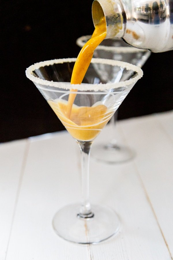A hand pouring a shaker of pumpkin martini into a martini glass.