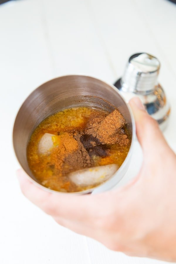 A hand holding a martini shaker with pumpkin spice martini ingredients in the shaker.