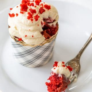 A red velvet cupcake with cream cheese frosting on a white plate with a fork full of the cake resting on the plate.