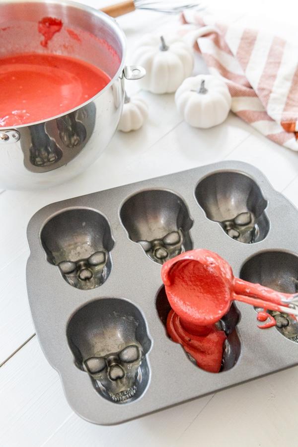 An ice cream scoop filled with red velvet cake batter filling a skull cake pan.