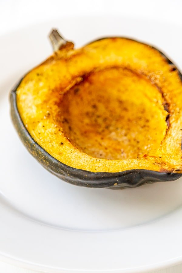 Half of a roasted acorn squash on a white plate.