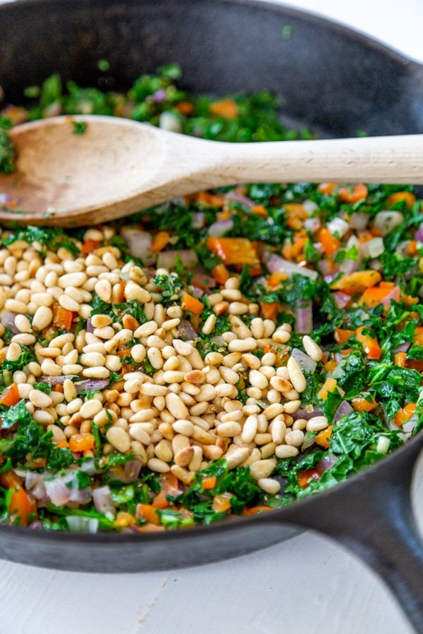An iron skillet with quinoa, vegetables, and toasted pine nuts.