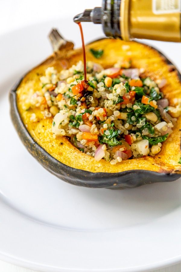 Balsamic glaze being poured over stuffed acorn squash.