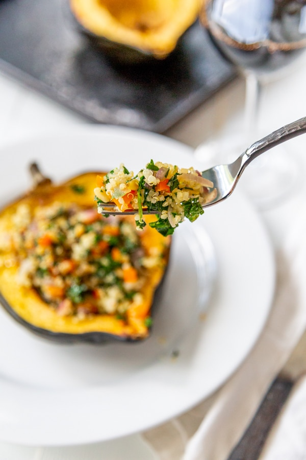 A fork with a serving of stuffed acorn squash and the squash below it on a white plate.