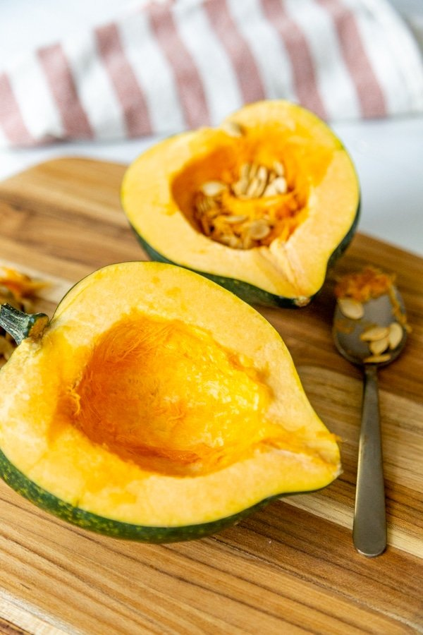 Two halves of an acorn squash on a wood board.