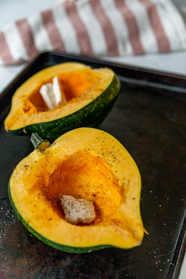 Two halves of an acorn squash on a baking pan with butter, salt, and pepper.