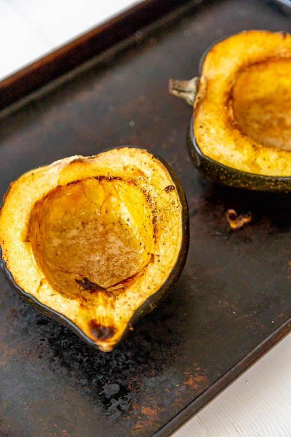 Two halves of roasted acorn squash on a baking sheet.