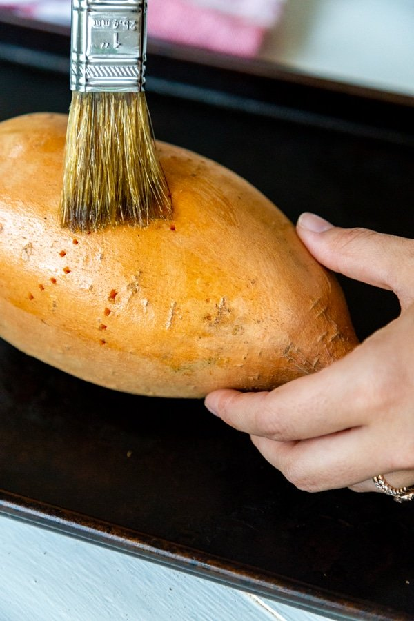 Hands brushing olive oil on a sweet potato.