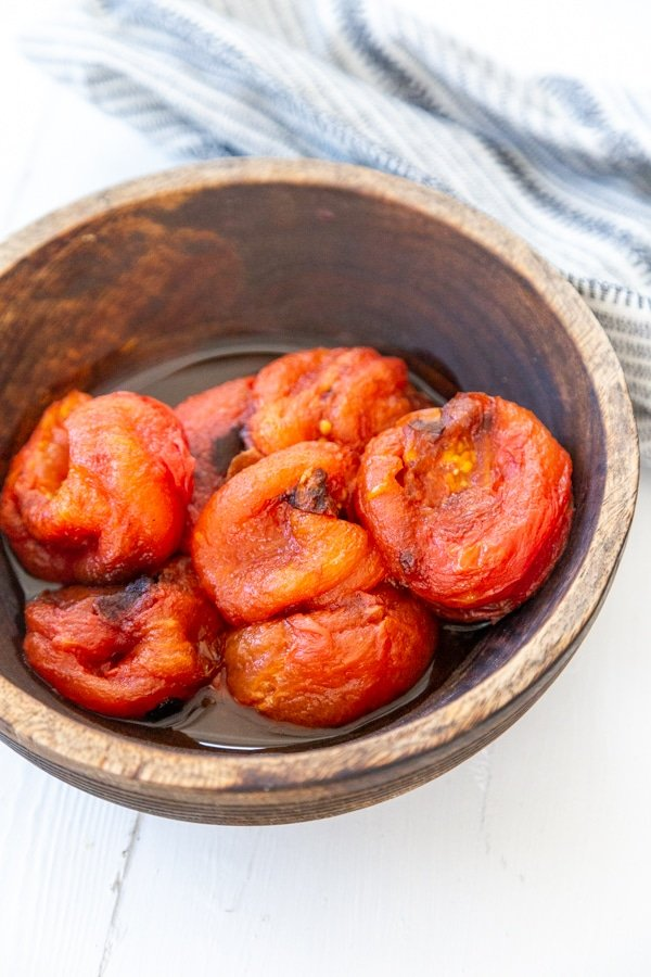 A wood bowl with roasted tomatoes.