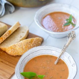 Two bowls of tomato soup with sliced bread on a board.