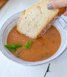 A bowl of tomato soup with a hand dipping a slice of bread in it.