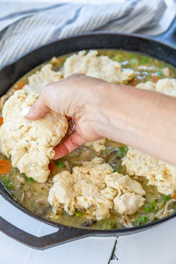 A hand placing drop biscuits over chicken and vegetable stew in an iron skillet.