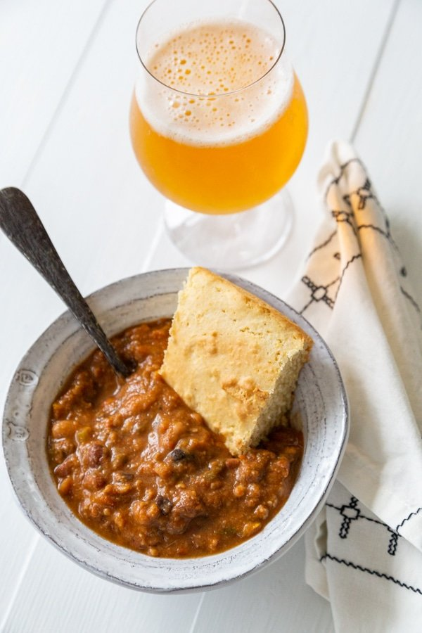 A white bowl with chili and cornbread and a glass of beer next to the bowl.