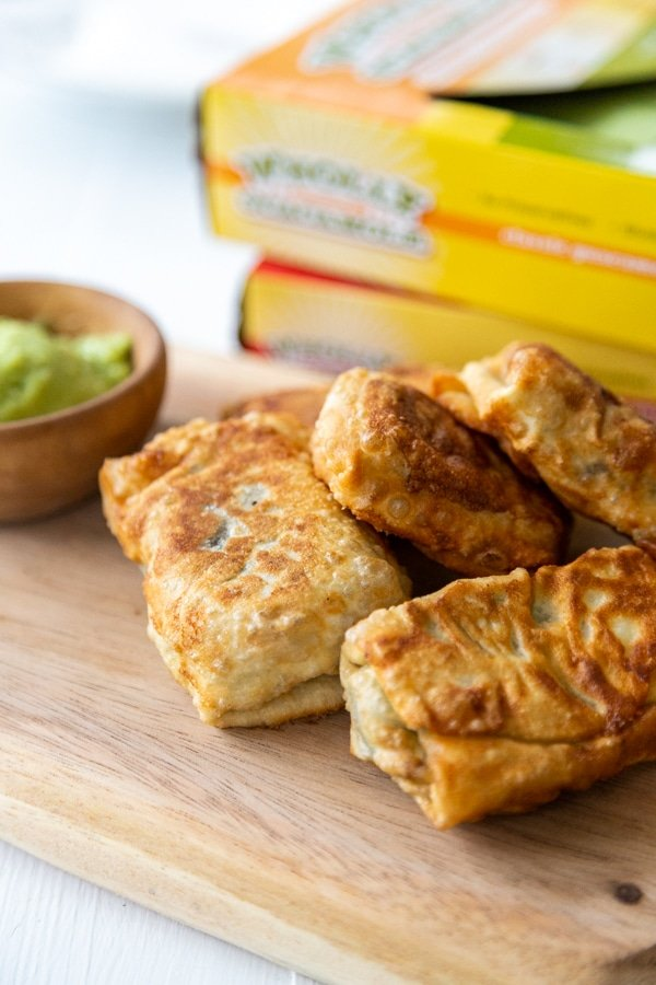 A stack of egg rolls on a wood board with a bowl of green dipping sauce and 2 boxes of guacamole in the background.