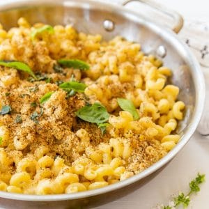 A copper pan of baked mac 'n' cheese with a bread crumb topping and fresh herbs.