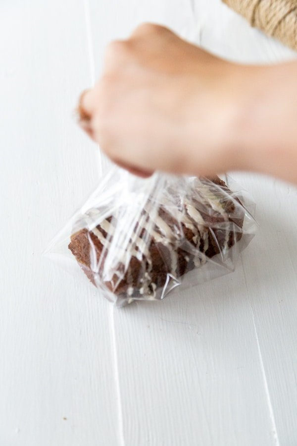 Two hands folding clear cellophane around a mini chocolate loaf cake with icing.