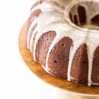 Half of a chocolate bundt cake with icing drizzled down the sides on a wood cake plate.
