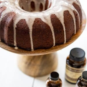 A chocolate bundt cake with vanilla glaze on a wood cake plate and bottles of Nielsen-Massey extracts next to it.