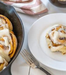An iron skillet with pumpkin cinnamon rolls and a white plate with a roll on it.