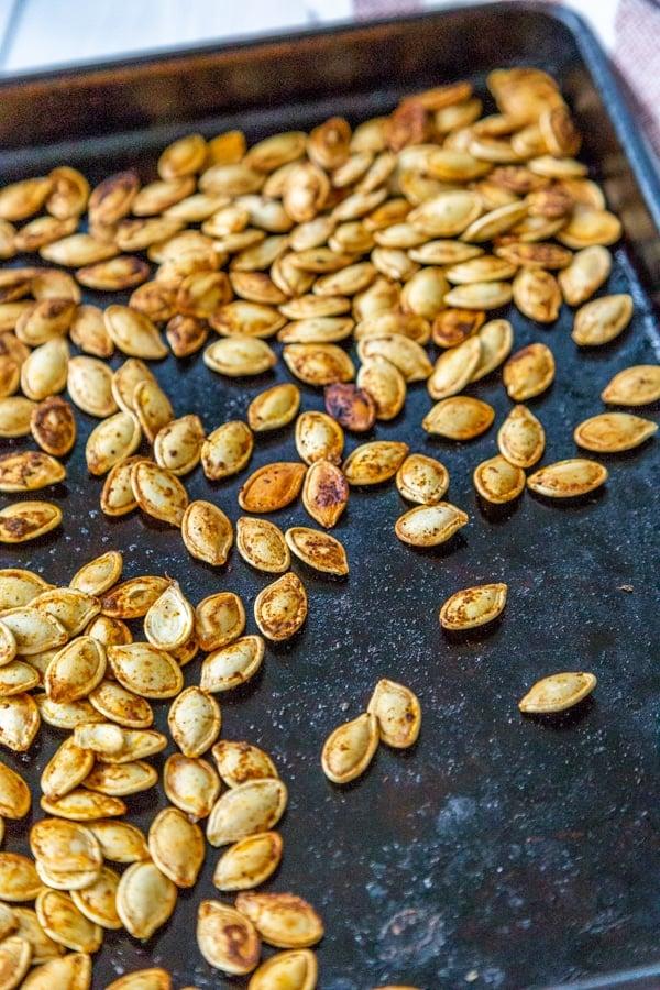 Roasted pumpkin seeds on a rimmed baking sheet.
