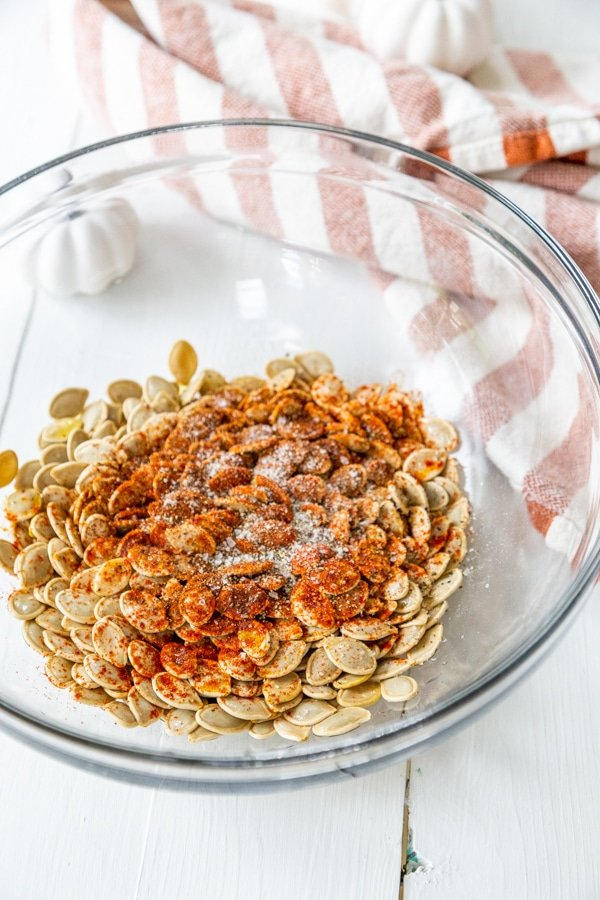 A glass bowl with pumpkin seeds and spice.