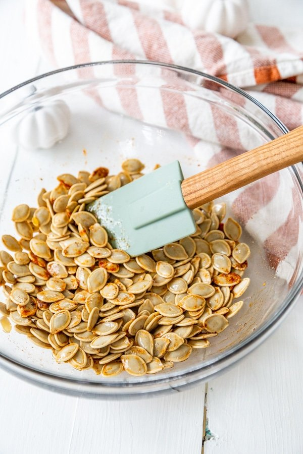 A spatula stirring spices and pumpkin seeds in a glass bowl.