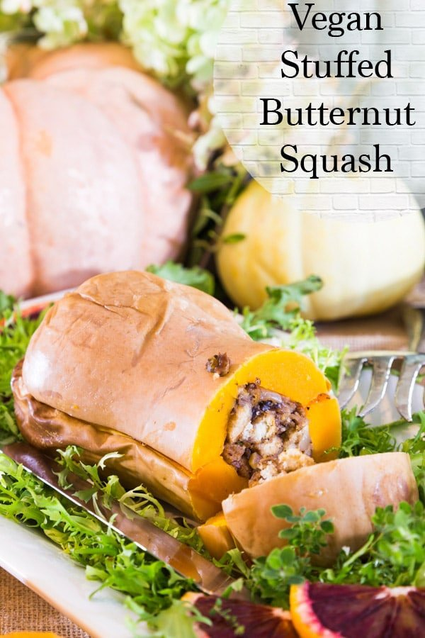 vegan stuffed butternut squash on a bed of greens and pumpkins in the background
