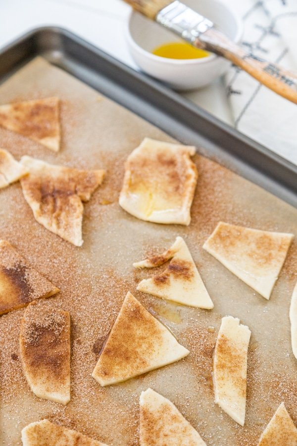 Unbaked pie crust chips with cinnamon sugar on a parchment lined baking sheet.