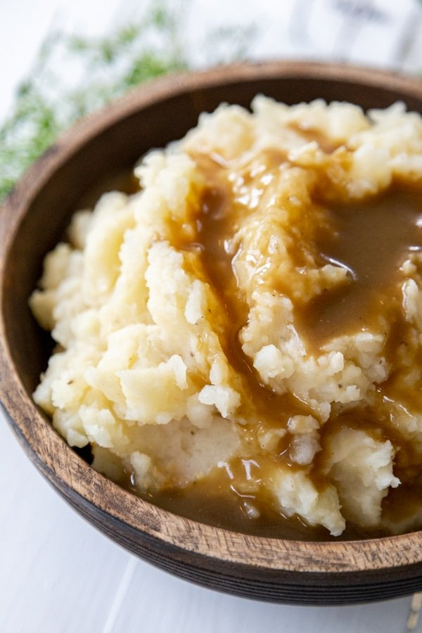 A wood bowl filled with mashed potatoes and brown gravy.