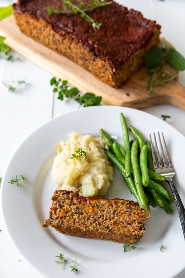A Pinterest pin with a slice of lentil loaf, green beans, and mashed potatoes on a white plate with the loaf in the background.