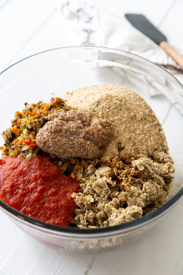 A clear glass bowl with the ingredients for a lentil loaf.